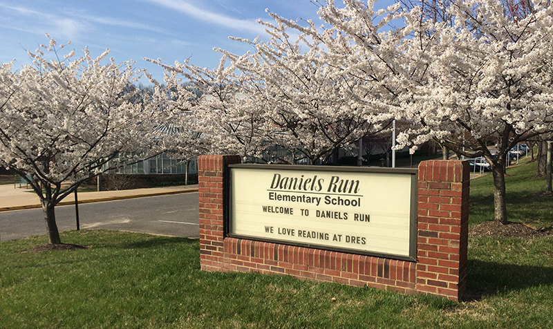 Photograph of the Daniels Run Elementary School sign that faces Old Lee Highway. The sign is mounted in brick housing and reads Welcome to Daniels Run, we love reading at DRES. The cherry trees on the school grounds are in full bloom with white blossoms, obscuring the view of the front of the school building.