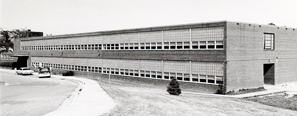 Black and white photograph of the front of Layton Hall Elementary School taken in 1956. One small tree graces the school grounds.